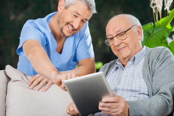 Happy male nurse helping senior man in using tablet computer at nursing home porch